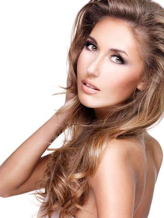 mujeres jovenes desnudas: Hermosa modelo sexy con el pelo largo y castaño le toca el hombro y lookes sobre ella. Aislados en blanco