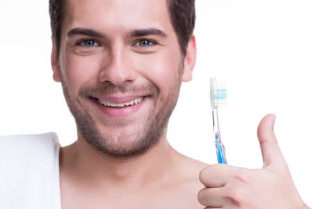 Сlose-up portrait of a happy young man with a toothbrush - isolated on white. photo