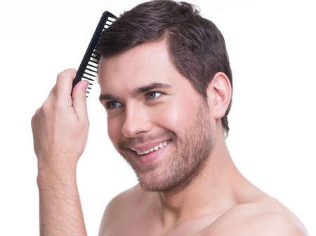 Portrait d'un jeune homme heureux se peigner les cheveux sur un fond blanc. Banque d'images