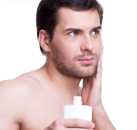 Young handsome man applying cream lotion on face - isolated on white. photo