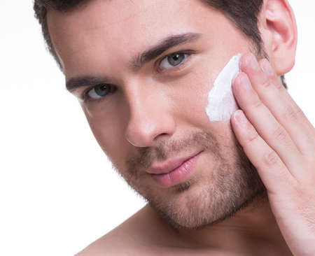 Portrait of young handsome man applying cream lotion on face - isolated on white. photo