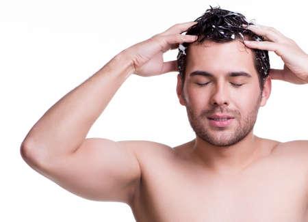 Mladí spokojený úsměv muž mytí vlasů se zavřenýma očima - na bílém.