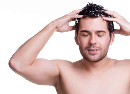 Young happy smiling man washing hair with closed eyes  - isolated on white.