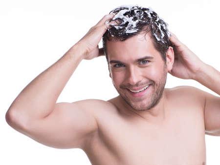 Jeune sourire heureux homme se laver les cheveux avec un shampooing - isolé sur blanc.