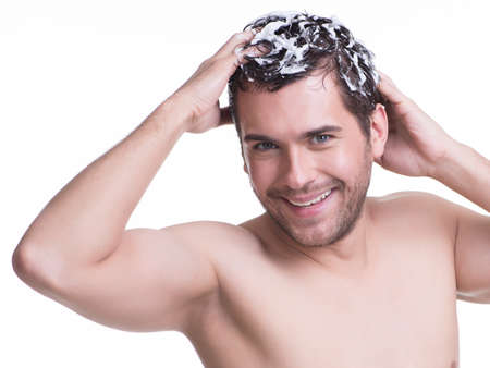 foam: Young happy smiling man washing hair with shampoo - isolated on white. Stock Photo