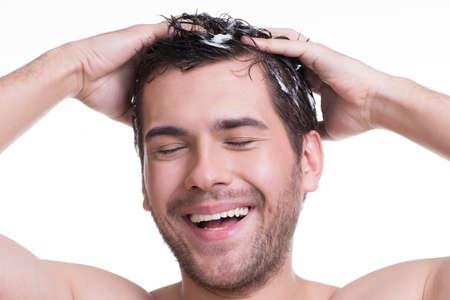 Jeune homme heureux sourire laver les cheveux, les yeux fermés - isolé sur blanc. Banque d'images