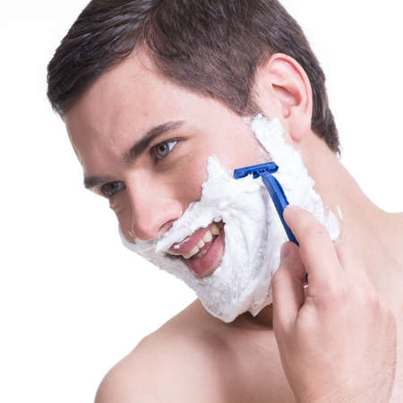 young man shaving the  beard with the razor photo