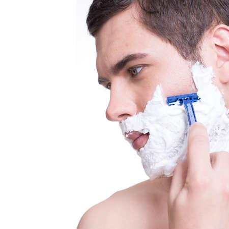 shaving cream: young man shaving the  beard with the razor - isolated on white Stock Photo