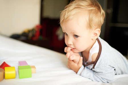 blonde yeux bleus: Portrait de mignon petit garçon jouant avec des blocs à la maison. Banque d'images