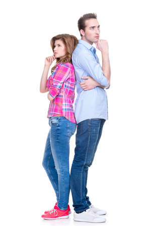Full portrait of thoughtful couple standing back to back isolated on white background.
