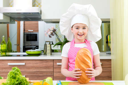 Happy little girl in pink apron with bread in her hands at the kitchen. photo