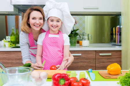 Portrait of happy young mother with daughter in pink apron cooking at the kitchen. photo