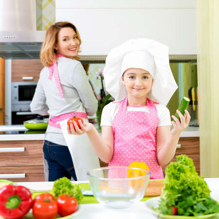 kitchen apron: Portrait of happy young mother with daughter in pink apron cooking at the kitchen. Stock Photo