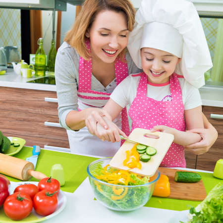 Cheerful smiling mother and daughter cooking a salad at the kitchen. Stock Photo