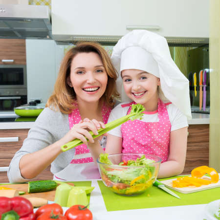 Portrait of attractive happy mother and daughter cooking a salad at the kitchen. photo