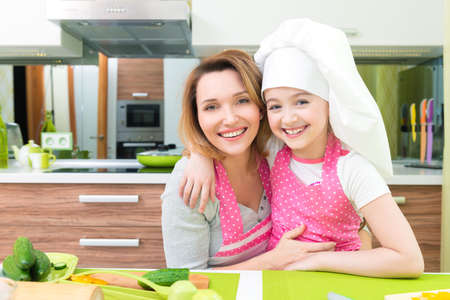 kitchen apron: Portrait of happy smiling mother and daughter in pink apron at the kitchen.