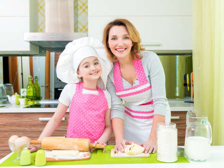Portrait of happy smiling mother and daughter making pies together at the kitchen. photo
