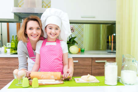 Attractive happy mother and daughter baking together at the kitchen. photo