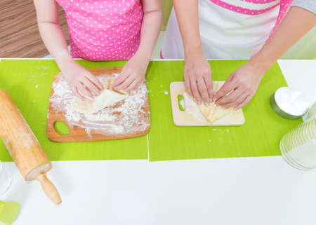 molded: Mother and daughter molded cakes at the kitchen. Stock Photo