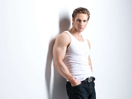 Fashion portrait of sexy young man in white shirt poses over wall with contrast shadows.