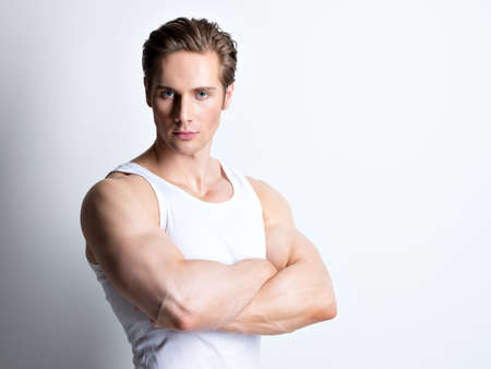 Fashion portrait of handsome young man in white shirt with crossed arms poses over wall.