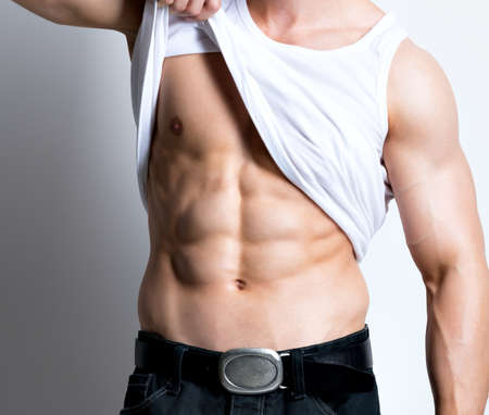 Handsome young sexy man in white shirt demonstrated torso poses at studio over white background. Stock Photo