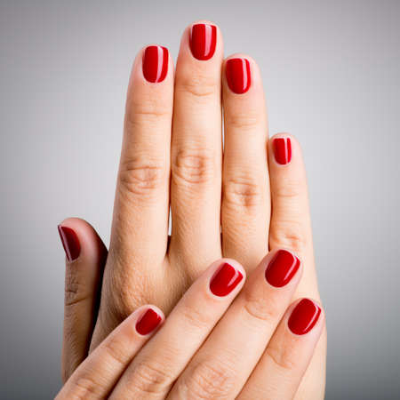 Closeup photo of a beautiful female hands with red nails Archivio Fotografico
