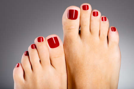Foto de detalle de una hermosa pies femeninos con pedicure rojo