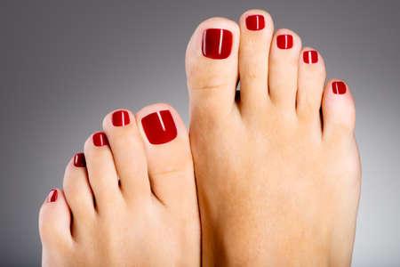 Foto del primo piano di una bella piedi femminili con il pedicure rosso Archivio Fotografico - 31989622