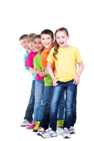 Gruppe glückliche Kinder in bunten T-Shirts stehen hinter einander auf weißem Hintergrund.