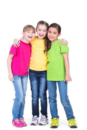 3 つかわいいかわいい笑顔の女の子立っている - 白で隔離され、カラフルな t シャツで。 写真素材