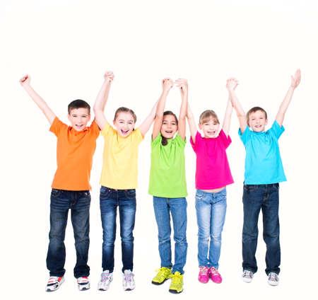 schoolchild: Groep van lachende kinderen met opgeheven handen in kleurrijke t-shirts eendrachtig samen - geïsoleerd op wit. Stockfoto