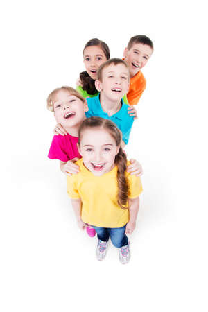 Group of happy children in colorful t-shirts standing together. Top view. Isolated on white.