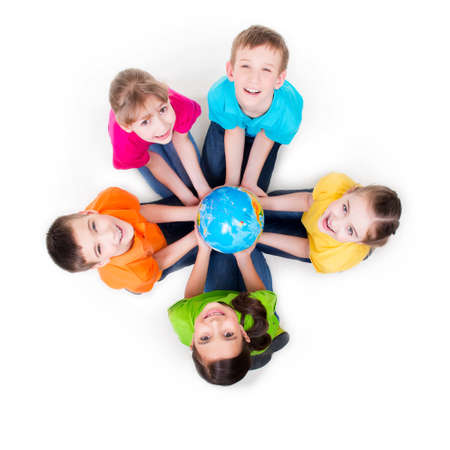 by hand: Group of smiling kids sitting on the floor in a circle with a globe in his hands - isolated on white.