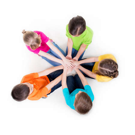 Group of smiling children sitting on the floor in a circle holding hands - isolated on white. Stock Photo