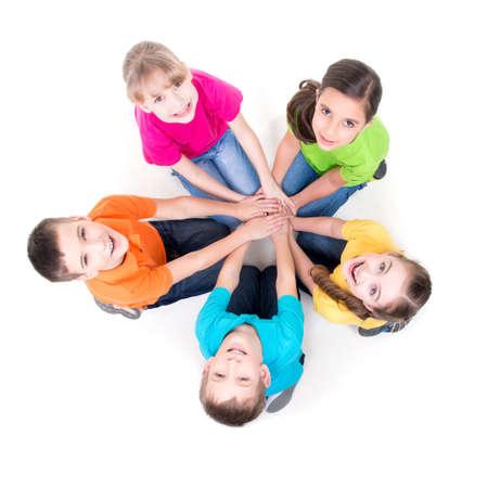 Grupo de niños felices que se sientan en el piso en un círculo que lleva a cabo las manos y que mira para arriba - aislado en blanco.
