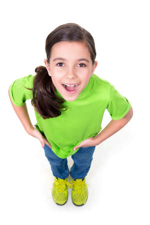 top angle: Portrait of cheerful little girl looking up in green t-shirt. Top view. Isolated on white background. Stock Photo