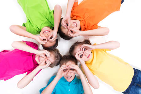 Five happy children lying on the floor in a circle with hands near eyes in bright t-shirts. Top view. Isolated on white. photo