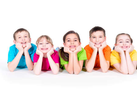 laying: Five beautiful smiling kids lying on the floor in bright colorful t-shirts -  isolated on white. Stock Photo