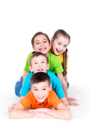 white person: Five beautiful smiling kids lying on the floor in bright colorful t-shirts -  isolated on white. Stock Photo