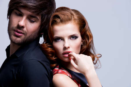 Closeup portrait of passionate young sexy couple in love posing at studio in evening clothes. photo
