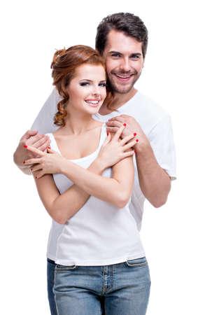 Belle jeune couple heureux vêtu d'un jean bleu et maillot blanc - isolé sur fond blanc.