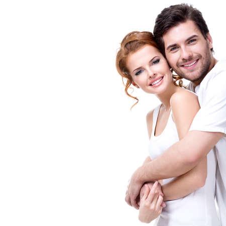 při pohledu na fotoaparát: Veselý šťastný mladý pár při pohledu na fotoaparát - na bílém pozadí. Reklamní fotografie