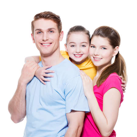 Happy smiling young family with little girl in colored shirts looking at camera - isolated on white. photo