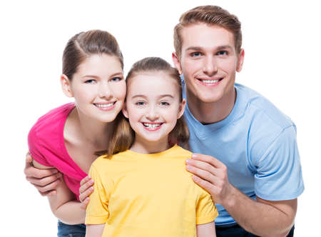 Portrait of the happy young family with child in multicolor shirts - isolated on white background. photo