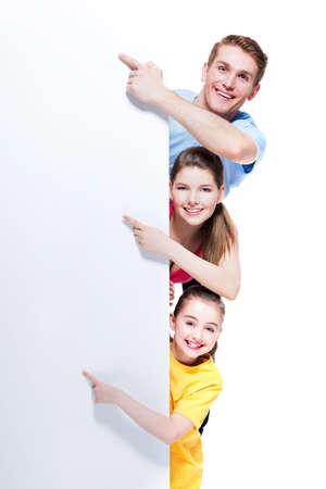 若い家族を指す指でバナー - 白い背景で隔離の笑顔の肖像画。 写真素材