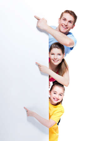 mother board: Portrait of young smiling family pointing by finger to the banner - isolated on a white background. Stock Photo