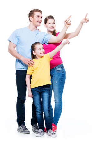 �aucasian: Happy young family with kid pointing finger up -  isolated on white background