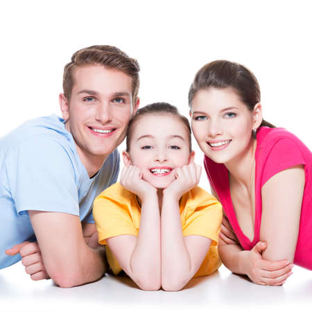 Portrait of happy smiling family with kid sitting in colorful shirt lying on the floor at studio - isolated on white. photo