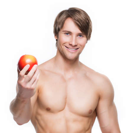 Portrait of young smiling bodybuilder holding apple in his hand - isolated on white background. photo
